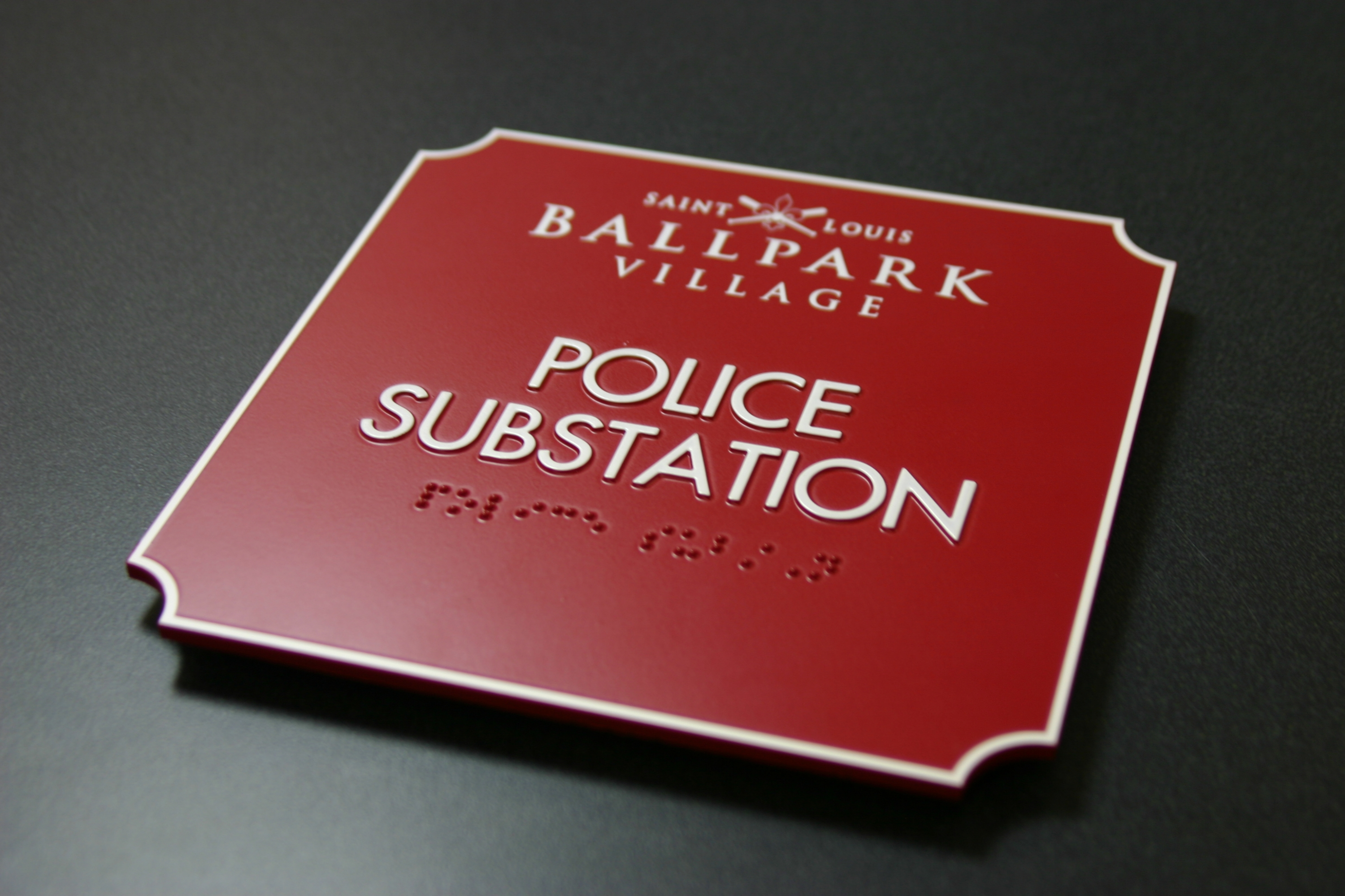 Photopolymer sign with raised border, text and braille. Surface applied paint and digitally printed graphic.