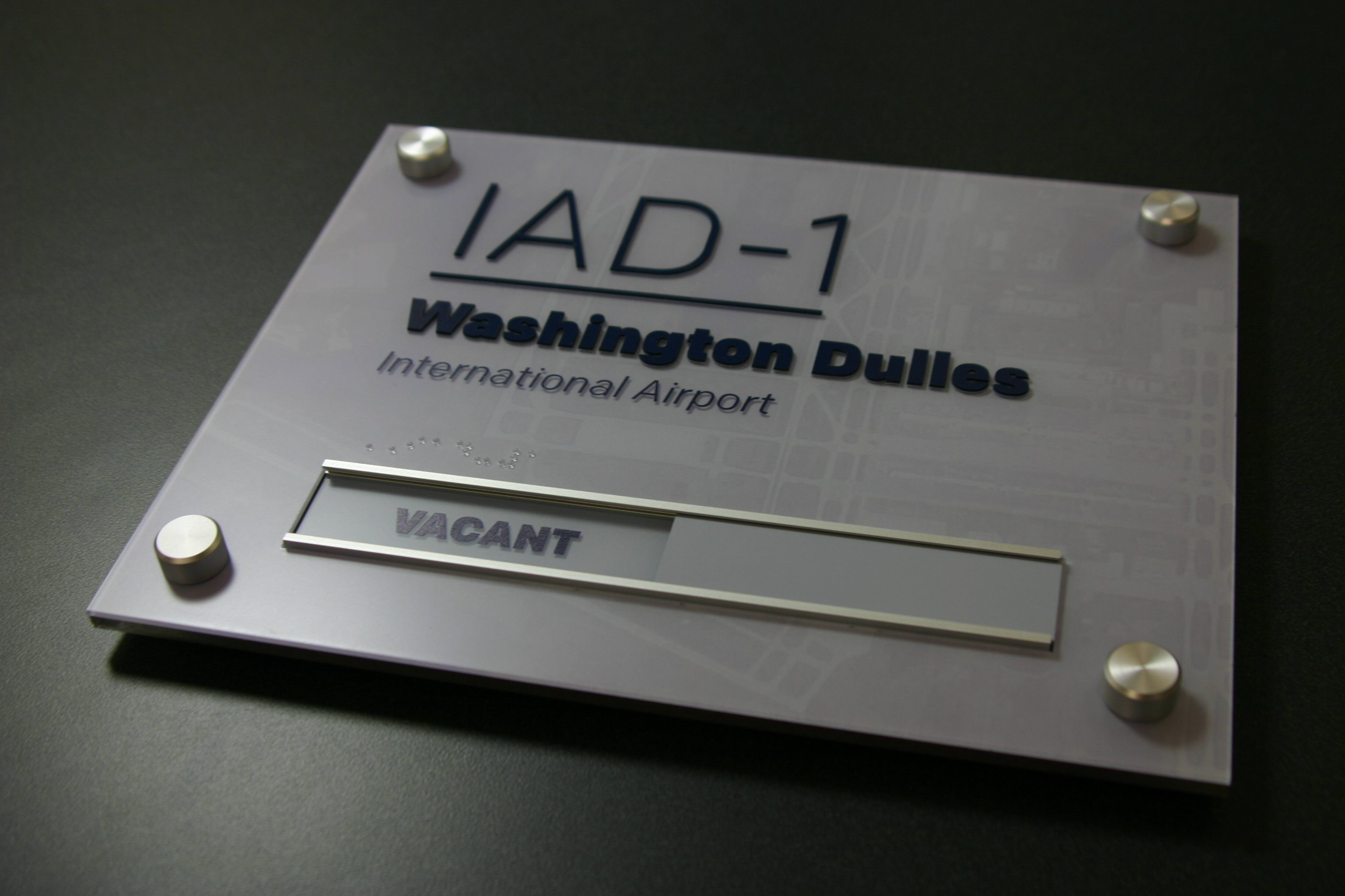 """.125"""" acrylic baseplate with .125"""" acrylic faceplate with subsurface graphics, surface applied raised text, changeable """"vacant/in use"""" sign and decorative standoff hardware."""
