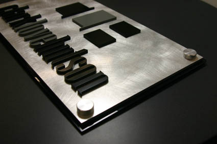 """Black acrylic baseplate with Chemetal laminate face, laser cut, surface painted .25"""" acrylic letters applied to face of sign with decorative satin silver standoff caps."""