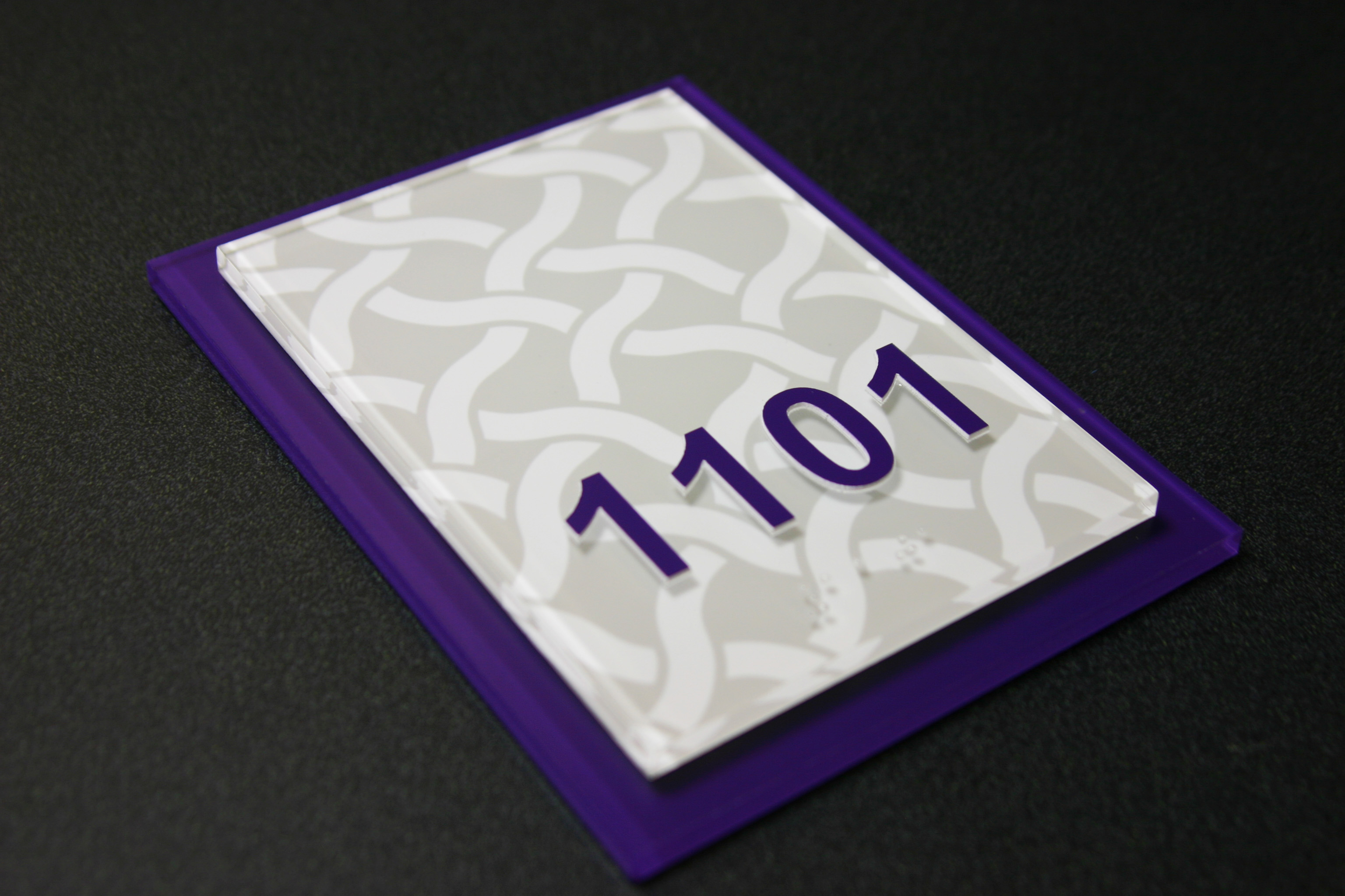 """.25"""" non-glare acrylic faceplate with subsurface digitally printed graphic, .25"""" non-glare acrylic backplate with subsurface paint. Surface applied raised text and friction fit clear raster braille."""