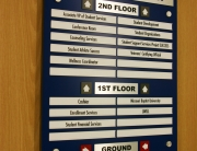 """.25"""" acrylic surface painted backplate. Brushed aluminum Chemetal applied to .25"""" thick black acrylic for permanent header and floor level designations. All department text is changeable utilizing sliding inserts in aluminum track extrusions. All text on header, floor levels and name strips is 1/32"""" raised, laser cut text applied to surface."""