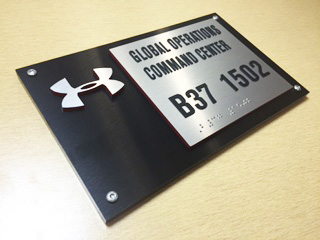 """.125"""" acrylic faceplate with brushed black Chemetal surface laminate. Accent plate with surface applied raised text and friction fit metal raster braille installed on brushed aluminum Chemetal laminated to .125"""" acrylic."""