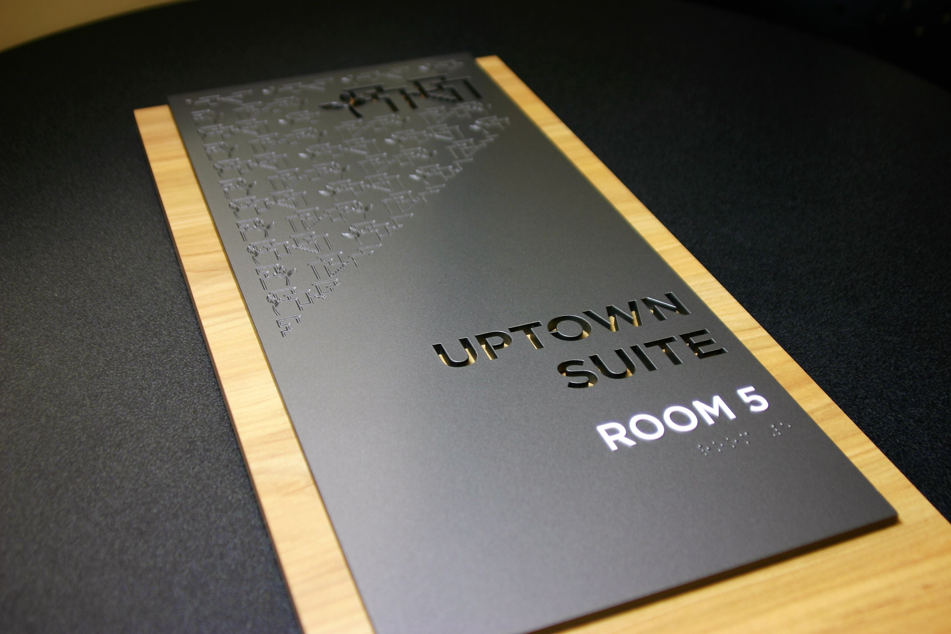 """.25"""" acrylic painted with laser engraved graphics and letter cutouts. Surface applied raised text and friction fit clear raster braille. .5"""" thick acrylic backplate with wood laminate face and painted edges."""