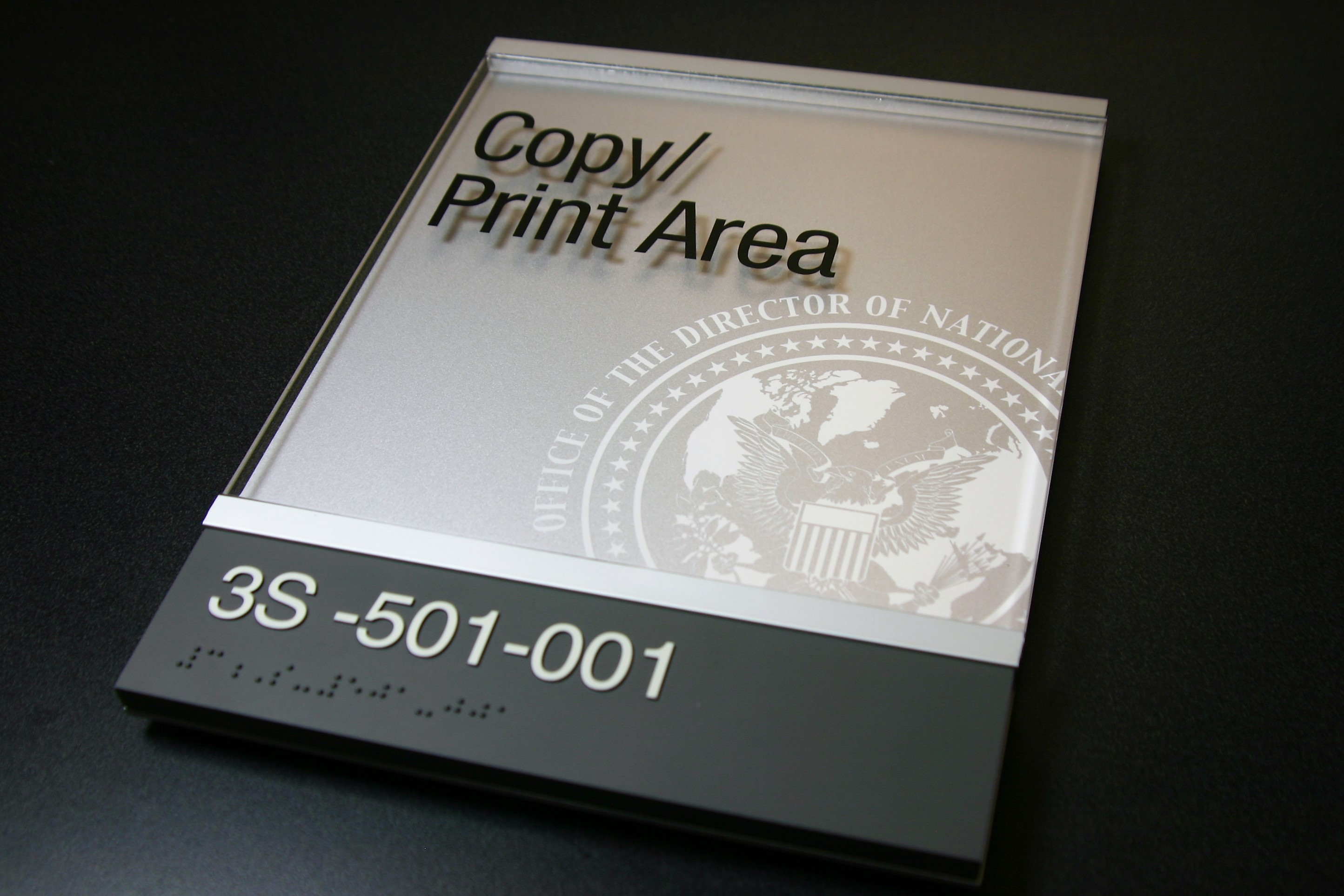 """.125"""" photopolymer lower section with integral text and braille. Upper section .125"""" clear acrylic with digitally printed text. Decorative aluminum bars that create sliding insert section at top. .125"""" surface painted acrylic backplate with digitally printed logo."""