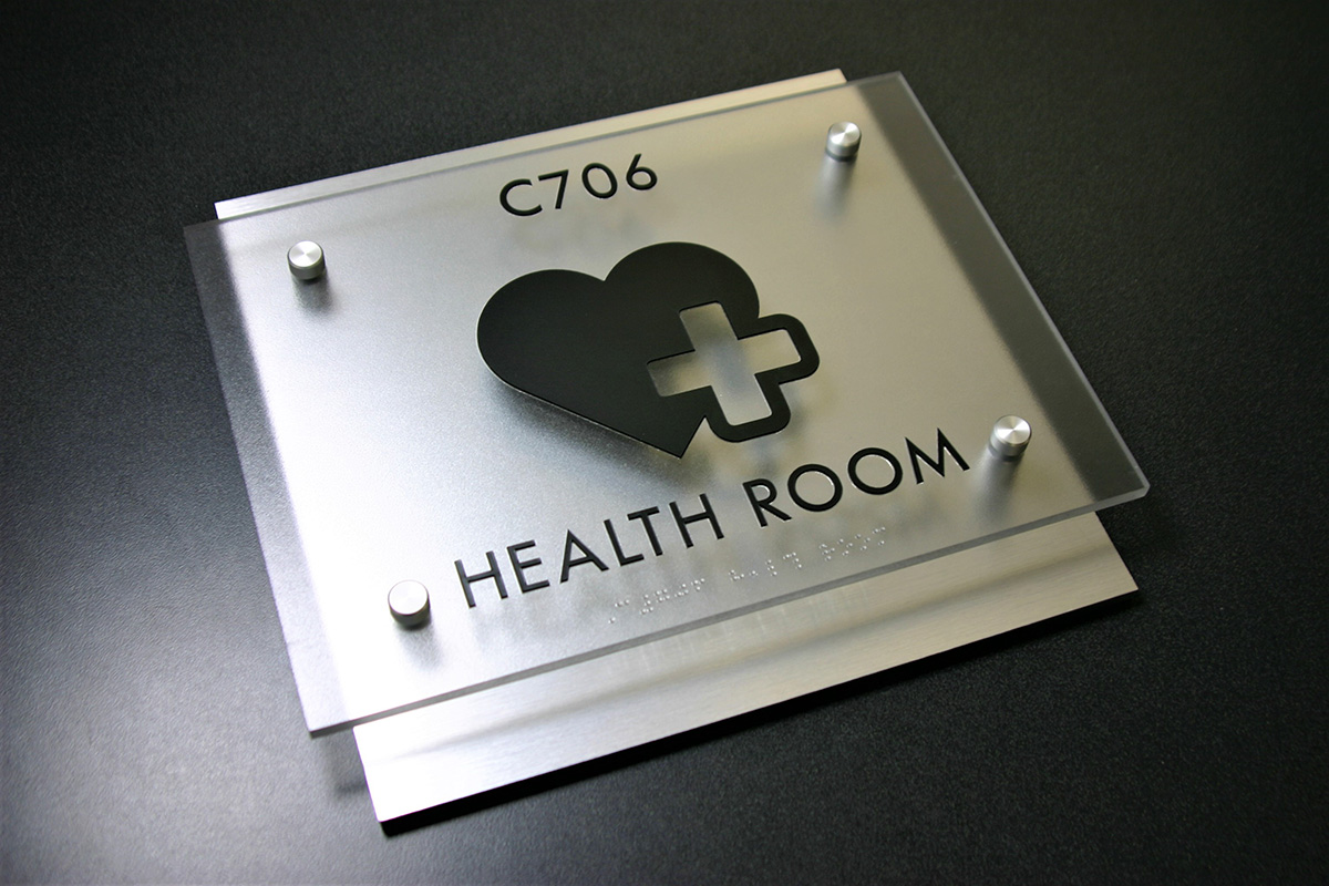 """.25"""" black acrylic backplate with brushed aluminum Chemetal laminate applied to top. .25"""" 3Form heavy matte faceplate with surface applied text and pictograph, friction fit clear raster braille beads and satin silver stand-off hardware."""