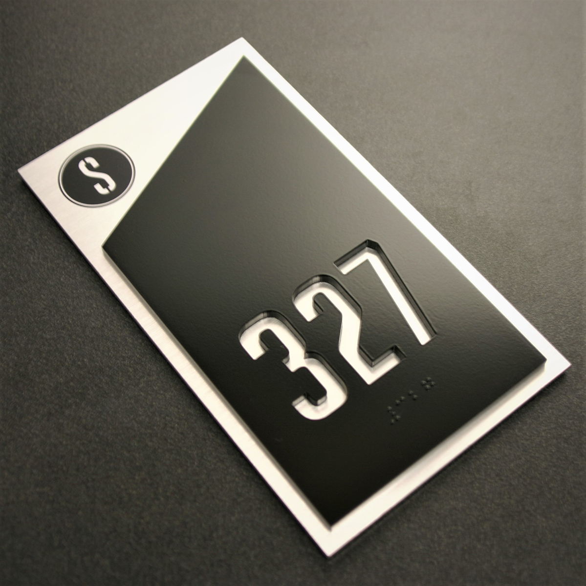 """.25"""" thick surface painted acrylic faceplate with laser cut numbers and friction fit black raster braille. .25"""" thick painted acrylic backplate with brushed aluminum laminate applied to surface. (Please note – Because room numbers are not raised in conjunction with the use of braille, this sign is not ADA compliant)."""