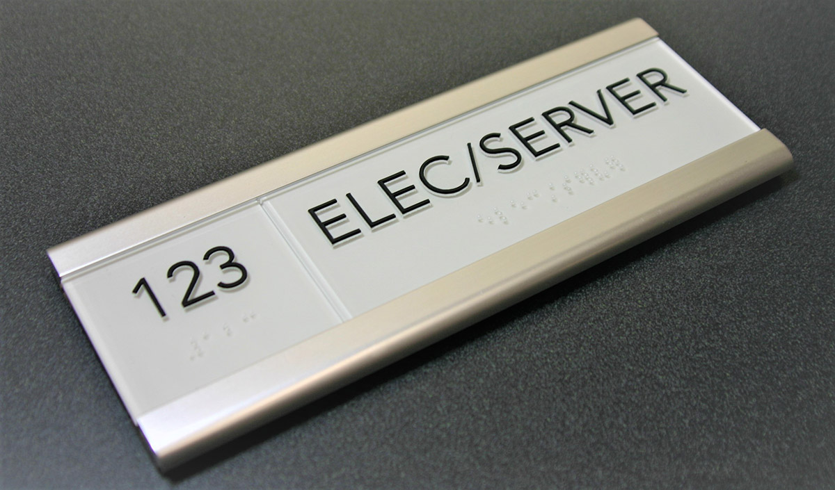 ".125"" thick nonglare acrylic faceplate with subsurface paint, surface applied raised text and friction fit clear raster braille with custom anodized silver aluminum sign frame."