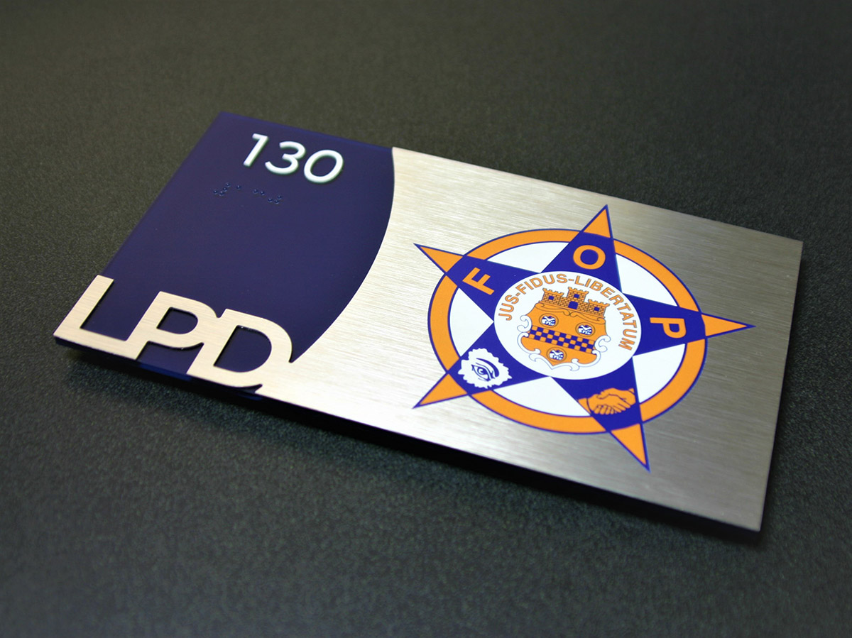 """.125"""" thick nonglare acrylic backplate with subsurface paint and Chemetal brushed aluminum laminate overlay with digitally printed text. Surface applied raised text and friction fit clear raster braille."""